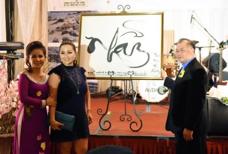 Bức họa chữ Nhẫn do bác Trần Chắt tặng Bs. Hồ Trâm đã dược Ls. Trinh La mua với giá $1000.Hình trái, từ trái: Christine Quỳnh, Ls. Trinh La, LM Michael Hoàng Nam.