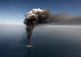 FILE - In this April 2010 file photo, oil can be seen in the Gulf of Mexico, more than 50 miles southeast of Venice on Louisiana's tip, as a large plume of smoke rises from fires on BP's Deepwater Horizon offshore oil rig. Deep-water drilling is set to resume near the site of the catastrophic BP PLC well blowout that killed 11 workers and caused the nation's largest offshore oil spill five years ago off the coast of Louisiana. (AP Photo/Gerald Herbert, File)